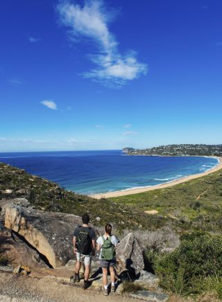 Couple enjoying a scenic coastal hike on the Barrenjoey Lighthouse Walk in Palm Beach, Sydney