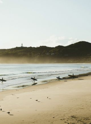 Surfers catching morning waves at Belongil Beach in Byron Bay, North Coast