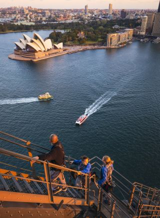 Friends enjoying a twilight BridgeClimb Sydney experience overlooking Sydney Harbour