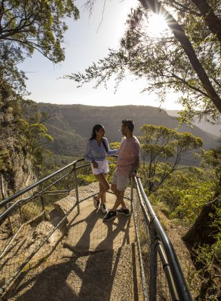 Couple enjoying views overlooking the Jamison Valley along the Giant Stairway Walking Track, Katoomba