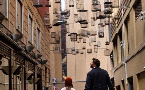Father and daugher walking underneath the Forgotten Songs artwork in Angel Place, Sydney