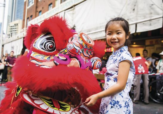 Young girl places a red packet into the mouth of the dragon during Chinese New Year in Chinatown, Sydney City